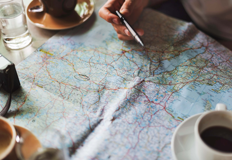 Landkarte mit Menschenhand & Stift