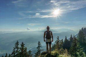 Ein Wanderer genieß den Ausblick von einem Aussichtspunkt auf den Bergen.