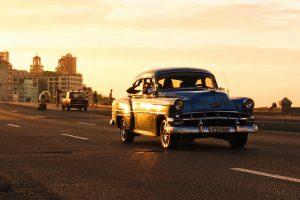 Ein Auto im Retrolook fährt, während eines Sonnenuntergangs, eine Straße entlang.