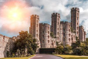 Eine große braune Burg. Dahiner strahlt die Sonne auf einen leicht bewölkten Himmel.