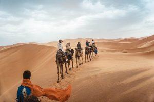 Menschen, in Gewändern, reisen auf Kamelen durch die Wüste.