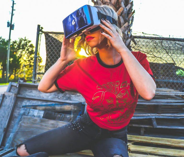 Frau im roten T-Shirt hat eine VR-Brille auf und schaut nach links.