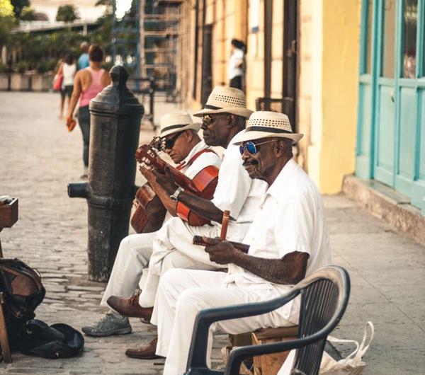 Kubaner sitzen auf einer Bank und spielen auf Instrumenten.