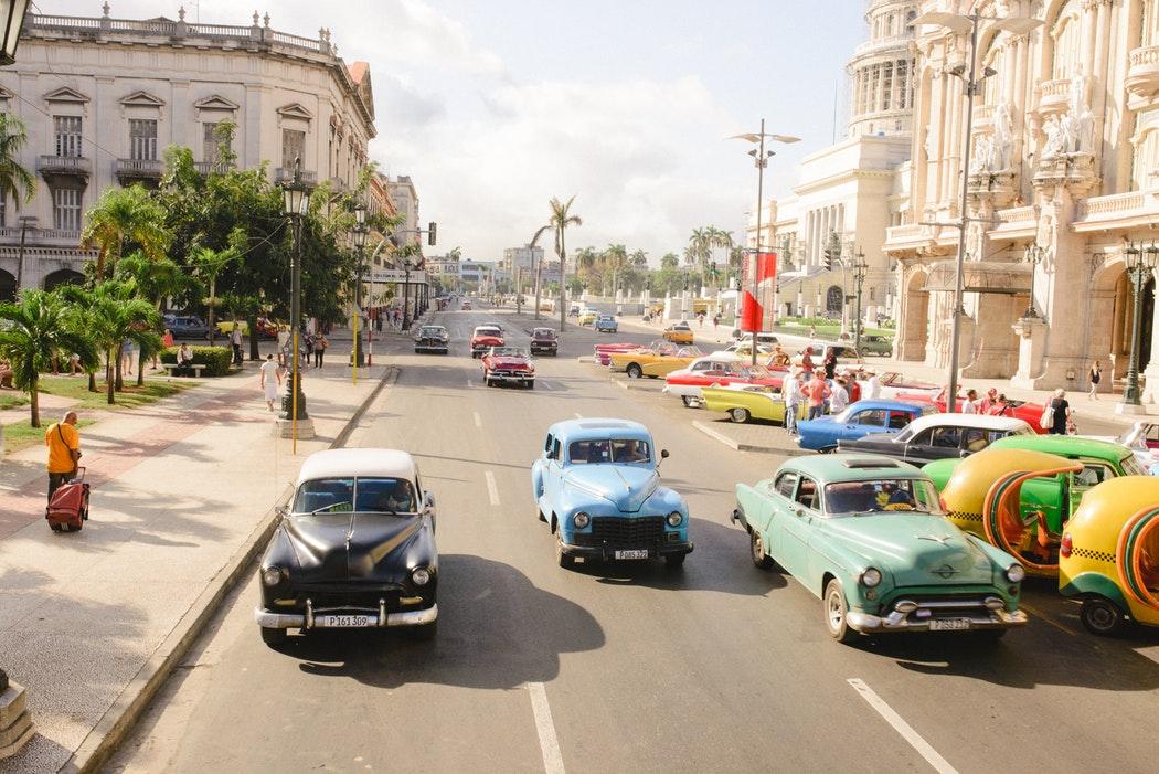 Auf einer mehrspurigen Straße fahren viele Oldtimer.