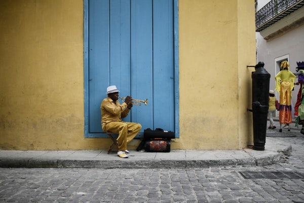 Ein Mann spielt vor einem Haus ein Instrument.
